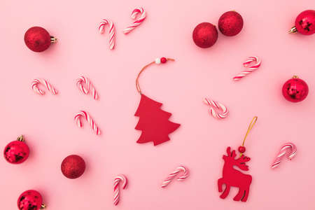 New Year composition. Red toys, candy canes and confetti on pink. Flat lay, top view. Zdjęcie Seryjne