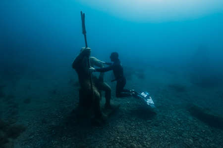 September 10, 2020. Anapa, Russia. Professional freediver in wetsuit with mono fin underwater in transparent sea. Freediving in Black sea