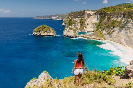 Traveler woman posing near Atuh beach and looks to ocean on Nusa Penida island, Indonesia.