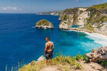 Traveler young man stay near Atuh beach and looks to ocean on Nusa Penida island, Indonesia. Standard-Bild