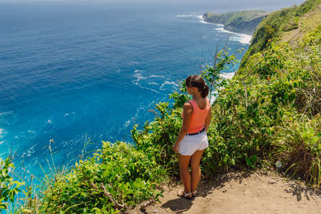 Woman stay on a high rock and looking out to sea. Kelingking beach, Nusa Penida, Indonesia.