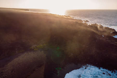 Aerial view of lava cliffs and ocean with sunset light and steam. Lanzarote, Canary Islands. Standard-Bild