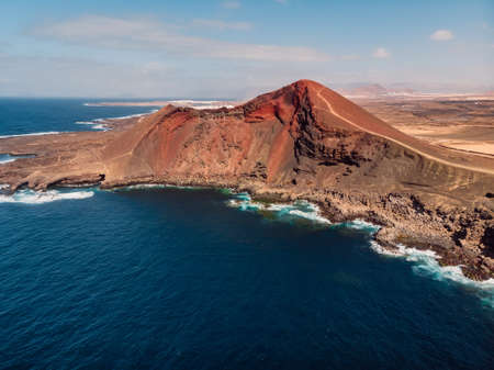 Old volcano with red rock and Atlantic ocean near La Santa, Lanzarote, Spain. Aerial view