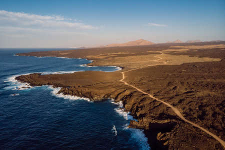 Aerial view of coastline with lava cliffs and ocean at sunset tones. Lanzarote, Canary Islands. Standard-Bild