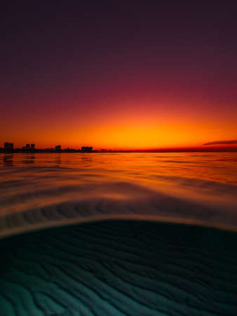 Split view with bright sunset and underwater sandy sea bottom.