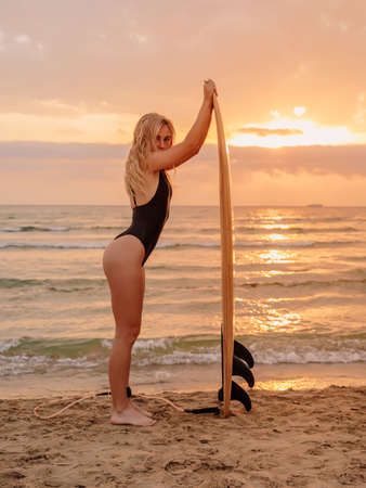 Surfer girl on sand beach with surfboard at warm sunset or sunrise. Attractive surfer women on beach
