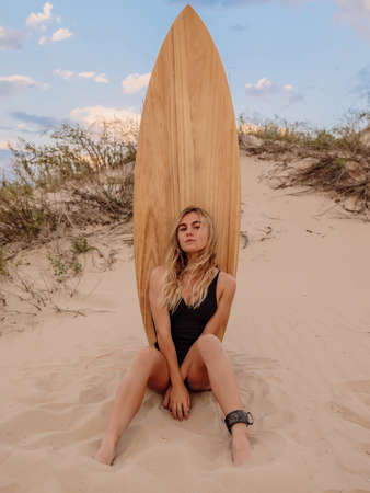 Surf girl in bikini posing with surfboard on a beach at sunset or sunrise. Surfer woman on coastline