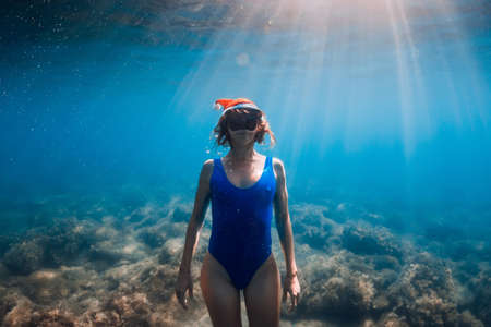 Happy freediver woman with Christmas cap posing underwater in blue ocean. Christmas holidays concept