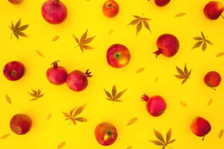 Pattern of pomegranate fuits with fall leaves isolated on bright yellow background. Flat lay, top view
