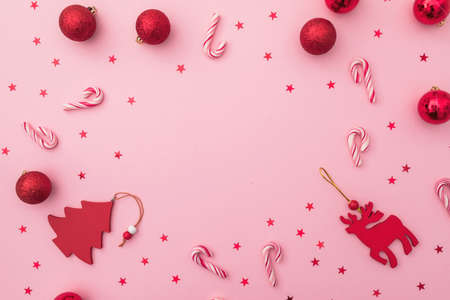 Christmas or New Year frame composition. Holiday toys, candy canes and confetti on pink. Flat lay, top view. Stok Fotoğraf