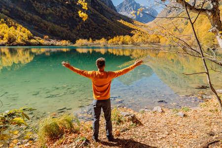 Happy man at the crystal lake in autumnal mountains. Mountain lake and hiker traveler Stok Fotoğraf