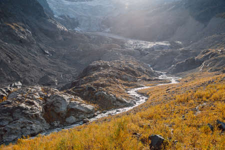 Rocky mountains, glacier and autumnal grass. High mountain landscape with river Stok Fotoğraf