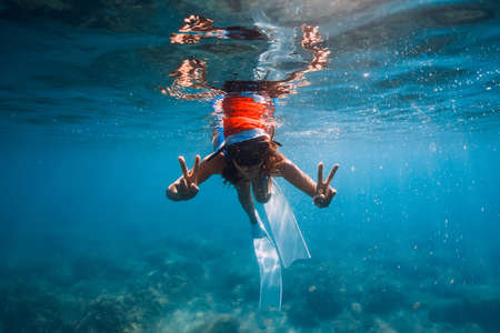 Freediver woman with Christmas cap posing underwater in blue sea. Christmas holidays