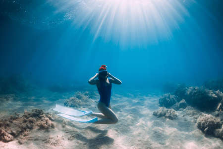 Christmas holidays party with freediver. Happy freediver woman with New year cap glides underwater with fins in blue ocean. Stok Fotoğraf