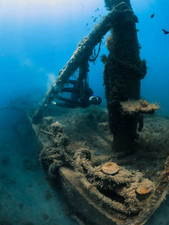September 10, 2020. Anapa, Russia. Professional freediver in wetsuit and wreck with seaweed underwater sea. Editöryel