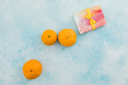 Mandarin fruits with gift box and blue background. Flat lay