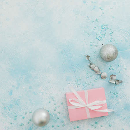 Christmas frame of stylish gift box and silver decoration on blue background. Winter holiday concept. Flat lay. Top view Stok Fotoğraf