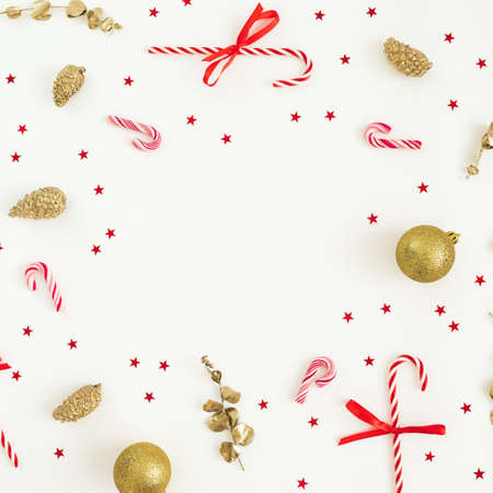 Christmas winter composition. Golden decoration with confetti and candy canes on white. Flat lay, top view. New Year holiday