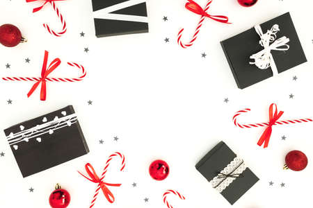 Christmas frame made of gifts with confetti and candy cane on white background. Flat lay. Top view. New Year concept