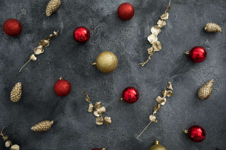 Christmas composition with golden and red decoration on dark background. Flat lay, top view