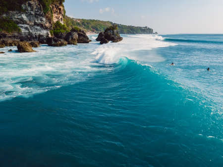 Barrel blue wave in ocean and cliff at background. Aerial view of surfing waves