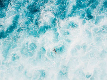 Aerial view of surfer on surfboard in blue ocean with foam. Top view