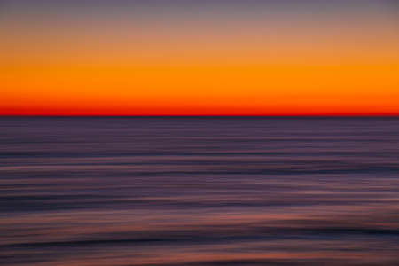Ocean with waves at bright sunset or sunrise shooting with long exposure