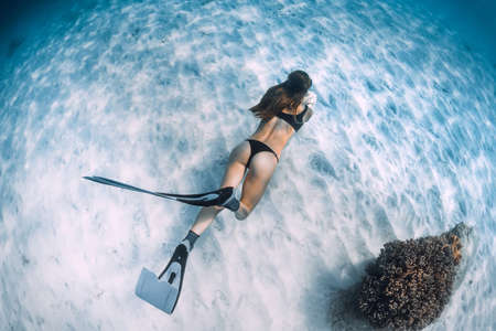 Woman freediver posing on sandy sea with fins. Free diving in Bahamas