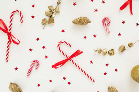 Christmas pattern with golden decoration, confetti and candy sugar canes on white. Flat lay, top view. New Year celebration