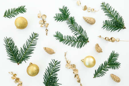 Christmas pattern made of evergreen branches and golden decoration on white background. Flat lay, top view