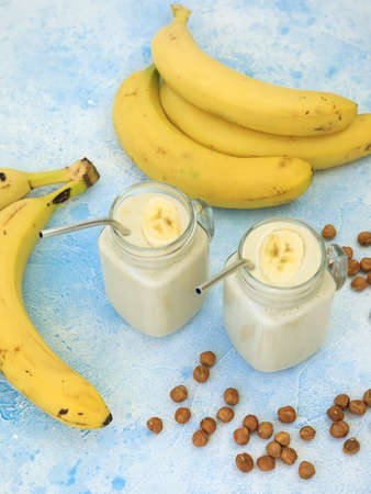 Trasty yogurt with banana and nuts, vegetarian food, diet and health concept
