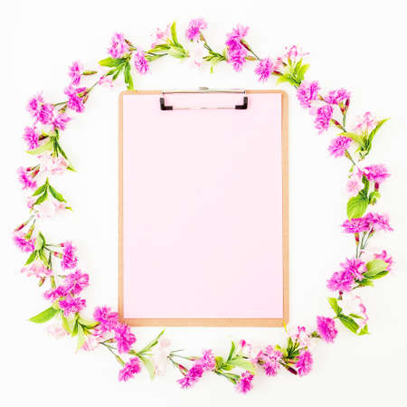 Flower frame of pink flowers and clipboard with pink paper on white background. Flat lay, top view