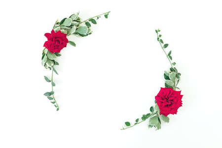 Round frame made of red roses and leaves on white background. Flat lay, Top view