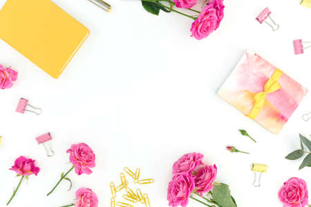 Frame composition with yellow notebook, pen, clips and roses flowers on white background. Flat lay. 写真素材