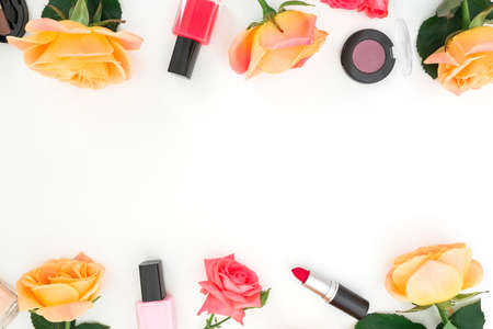 Orange roses flowers and beauty cosmetics on white background. Top view. Flat lay