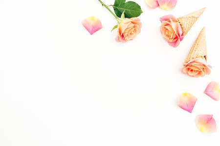 Roses flowers and wafle cones on white background. Flat lay, top view. Copy space