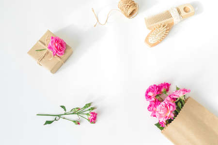Beauty frame of pink roses with hairbrush, tassel and gifts on white background. Flat lay, top view 写真素材