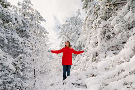 Happy woman standing among snowy trees in winter forest. Traveler woman play with snow