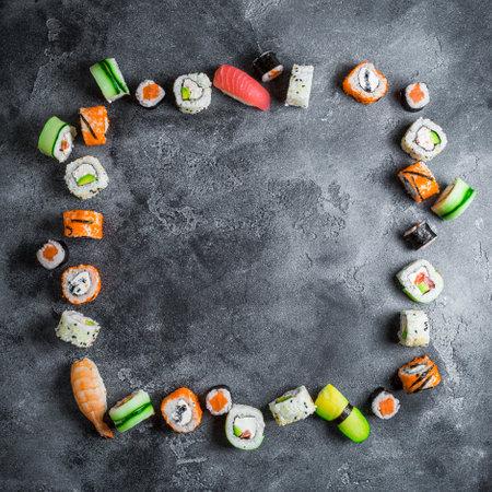 Sushi frame on dark background. Sushi rolls, nigiri, raw salmon steak, rice, and avocado. Flat lay. Top view 写真素材