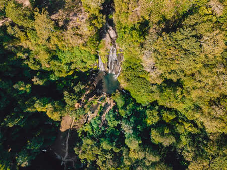 Waterfall with small lake in tropical jungle at Bali. Indonesia. Aerial drone view 写真素材