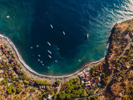 Aerial view of Balinese town with blue sea and boats. Amed, Bali