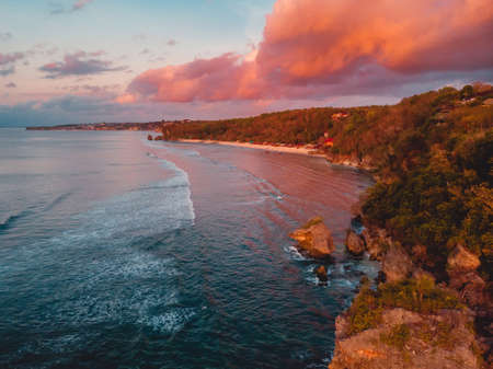 Aerial view of rocky coastline with cliff, ocean and bright clouds at warm sunset on Bali