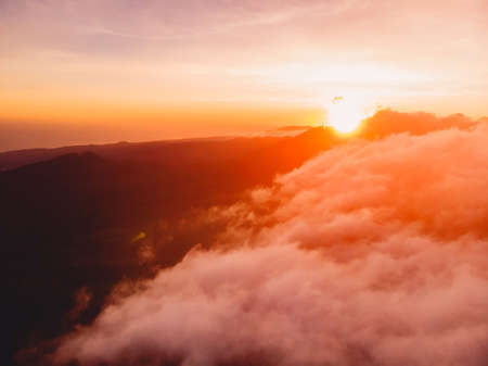 Aerial view over clouds with warm sunrise