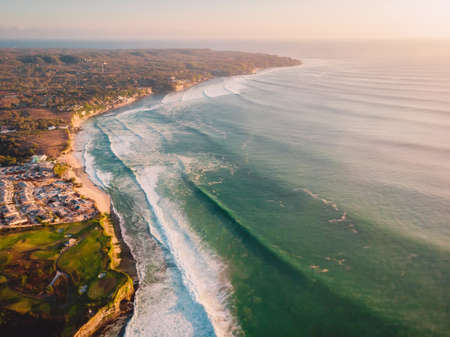 Aerial view of coastline at warm sunset and Bali beach. Perfect ocean waves for surfing