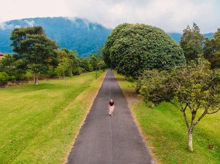 Woman in dress walking on road in tropical garden at Bali