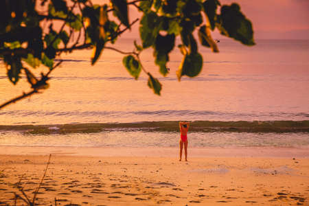 Slim woman relaxing on the tropical beach at sunset or sunrise. Bikini woman in Bali beach