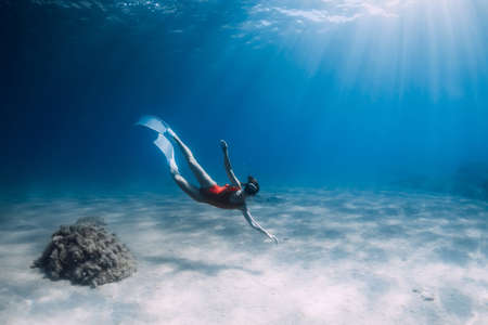 Attractive woman freediver with white fins posing underwater in tropical sea. Zdjęcie Seryjne