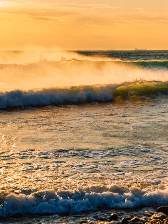Ocean waves at warm sunset or sunrise. Waves and wind with evening light
