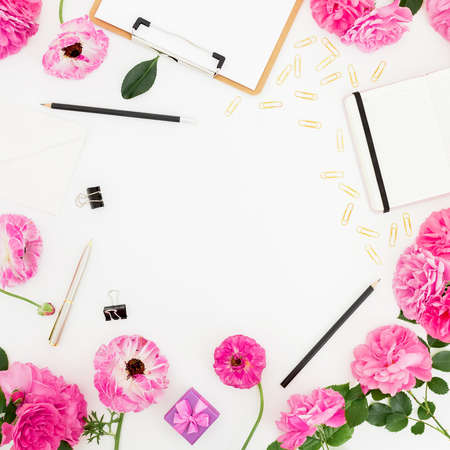 Stylish home workspace with clipboard, notebook, pink flowers and accessories on white background. Flat lay, top view.