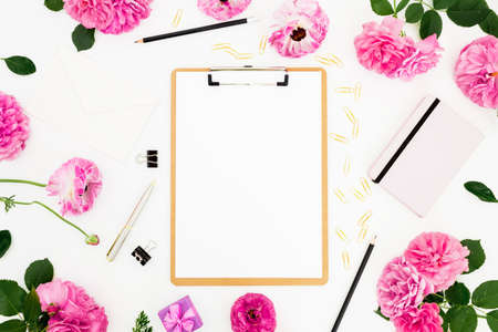 Home workspace with clipboard, notebook, pink flowers and accessories on white background. Flat lay, top view.